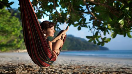landscape scene: Pretty woman is laying on the hammock on the tropical ocean background.