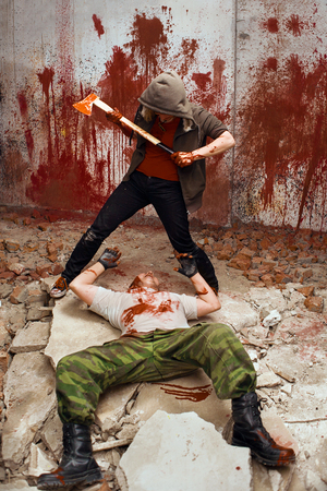 maniac: Bloody maniac with the axe is going to kill a victim Stock Photo