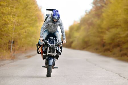 Stunt rider making stoppie on the autumn forest background