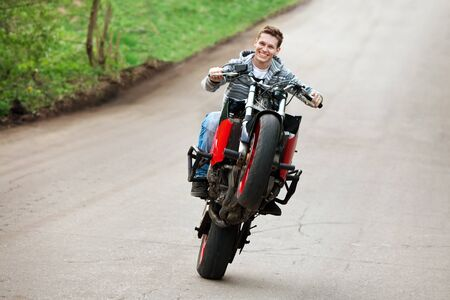 stunt: Stunt rider is riding on the one wheel of his motorbike