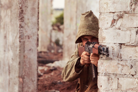 ak 74: Insurgent in hood with the  machine gun is aiming. Ruined city background.