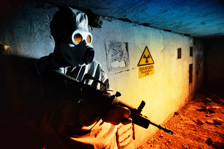 chemical hazard: Soldier in protective clothes and mask with the rifle on the ruined bunker background. Stock Photo