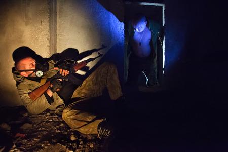 mascara de gas: Soldado con el fusil en la máscara de gas en el primer plano. Zombie sangrienta en la oscuridad. Foto de archivo