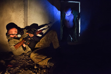 gas mask: Soldier with the rifle in the gas mask on the foreground. Bloody zombie in the dark. Stock Photo