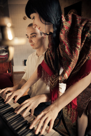 Man and woman are playing piano together. Focus point on the man. photo