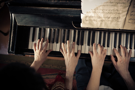 Man and woman are playing piano together Stock Photo