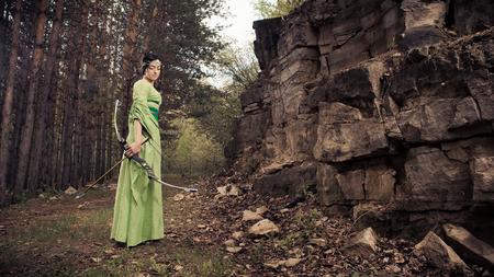 숲 배경에 마법의 활을 가진 엘 프 여자.