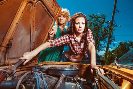 mecanico: Hermosa mujer mecanic está reparando un coche otra mujer está mirando.
