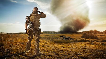 Soldado con el fusil está mirando el humo de debajo de la ciudad. Edificios en ruinas en el fondo.