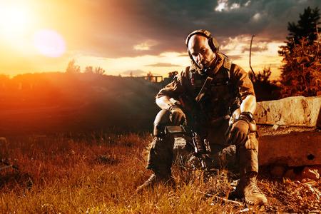 soldado: Soldado americano con el rifle M4 est� teniendo un resto. Puesta de sol en el fondo. Foto de archivo