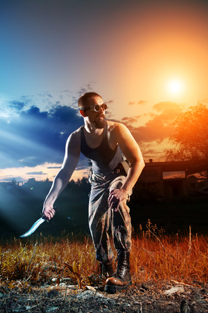 Powerful man with the big knife on the sunset background. Stock Photo