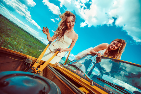 car breakdown: Beautiful women with tools are repairing a car on the rural road