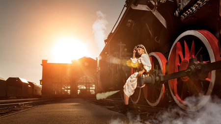 Woman in the vintage dress is sitting on the locomotive's wheel. Station on the background. Artistic lens flares are the part of composition. Banco de Imagens