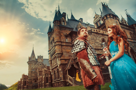Mooie prinses geeft zwaard aan haar dappere ridder. Oude kasteel op de achtergrond. Stockfoto
