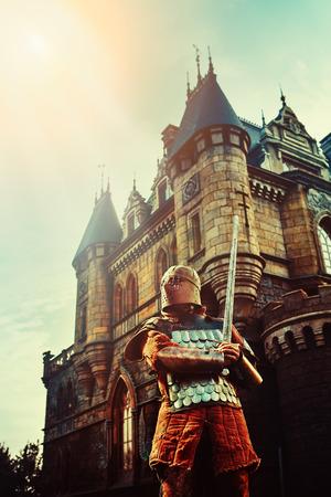 castello medievale: Cavaliere medioevale con la spada sulla dell'antico castello di fondo Archivio Fotografico