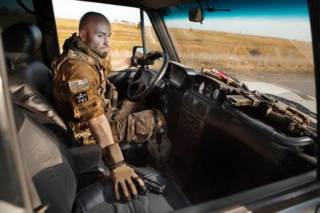 soldado: Soldado Calvo en uniforme está conduciendo vehículo militar.
