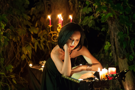 woodland  horror: Beautiful witch is reading the book of magic. Dark forest on the background.