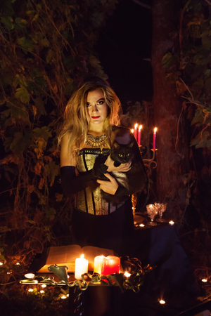 woodland  horror: Beautiful witch with the black cat is reading the book of magic. Dark forest on the background.