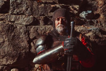 cavaliere medievale: Vecchio Re medievale in armatura con la spada sullo sfondo rocce. Punto focale sul viso.