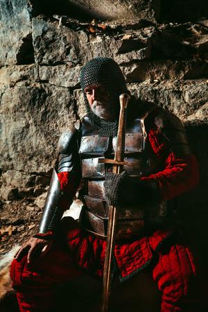 rey medieval: Rey medieval en la armadura con la espada est� sentado sobre pieles cerca del fuego de campamento Foto de archivo