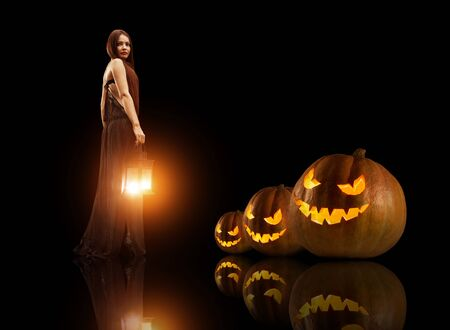 beldam: Bella strega con la lanterna magica. Zucche di Halloween su sfondo. Archivio Fotografico