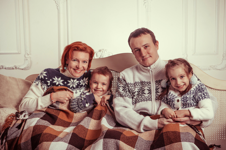 family sofa: Beautiful family in the sweaters is laying on the sofa under the blanket.