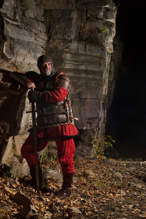 rey medieval: Old medieval King in armor with sword on the rocks background. Foto de archivo