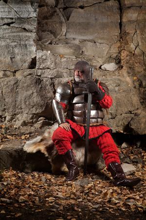 caballero medieval: Rey medieval en la armadura con la espada en el fondo de rocas.