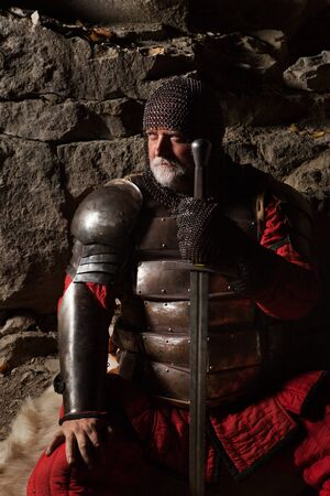 rey medieval: Old medieval King in armor with sword is sitting on furs