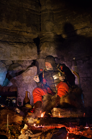 rey medieval: Old medieval King in armor with dish is sitting on furs near the camp fire and having a lunch