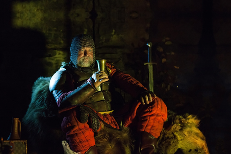 cavaliere medievale: Vecchio Re medievale in armatura con il piatto è seduto sulle pellicce vicino al fuoco da campo e bere vino