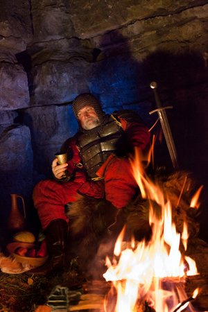 rey medieval: Old medieval King in armor with dish is sitting on furs near the camp fire and drinking wine Foto de archivo