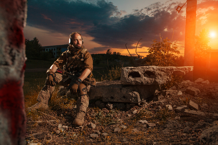 soldiers: American soldier with the M4 rifle is having a rest. Sunset on the background.