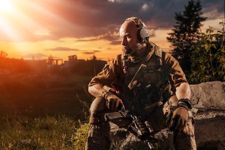 soldado: Soldado americano con el rifle M4 está teniendo un resto. Puesta de sol en el fondo. Foto de archivo