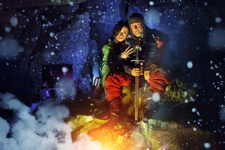 snow falls: Medieval King in armor with sword is sitting on furs near the camp fire with his princess. Snow falls. Stock Photo