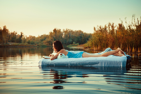 nighty: Pretty woman is laying on the floating bed and reading a book. Summer sunset on the background. Stock Photo