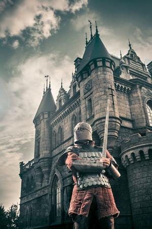 cavaliere medievale: Cavaliere medioevale con la spada sulla dell'antico castello sullo sfondo. Bassa post-elaborazione di contrasto. Archivio Fotografico