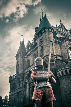 medieval: Medieval knight with the sword on the ancient castle background. Low contrast post processing. Stock Photo