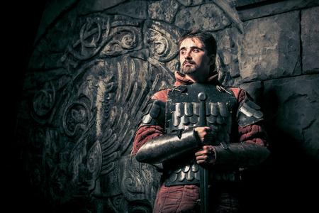Cavaliere medioevale con la spada sulla dell'antico castello sullo sfondo. Bassa post-elaborazione di contrasto. Archivio Fotografico - 49249068