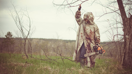 Walking maniac with the chainsaw dressed in a dirty bloody raincoat. Stock Photo