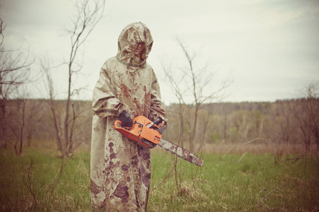 maniac: Walking maniac with the chainsaw dressed in a dirty bloody raincoat. Low-contrast post-processing.