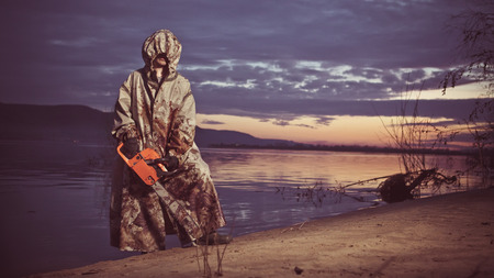 capote: Maniac with the chainsaw dressed in a dirty bloody raincoat. Artistic toning. Stock Photo