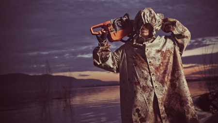 maniac: Maniac with the chainsaw dressed in a dirty bloody raincoat. Artistic toning. Stock Photo
