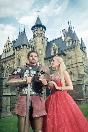 vestidos de epoca: Caballero medieval con su amada dama. Antiguo castillo en el fondo.