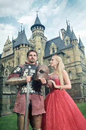 medieval sword: Medieval knight with his beloved lady. Ancient castle on the background.