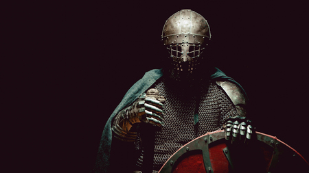 armor: Medieval knight in the armor with the sword and shield. Artistic toning. Stock Photo