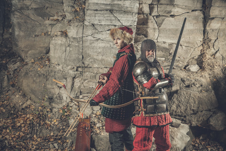 squire: Old knight with the sword and his squire armed with bow. Artistic toning.