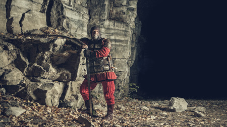 one armed: Old medieval King in armor with sword on the rocks background. Stock Photo