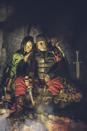 Medieval King in armor with dagger is sitting on furs near the camp fire and looking at fire with his princess. Artistic toning.