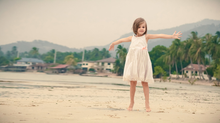 expressing: Young happy girl in white dress is expressing positivity on the tropical beach